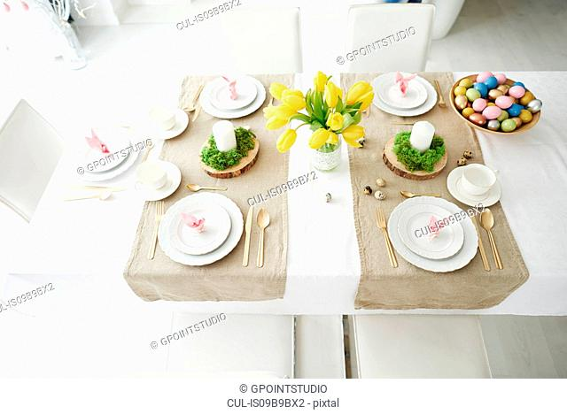 Bunny ear napkins and bowl of colourful easter eggs on dining table