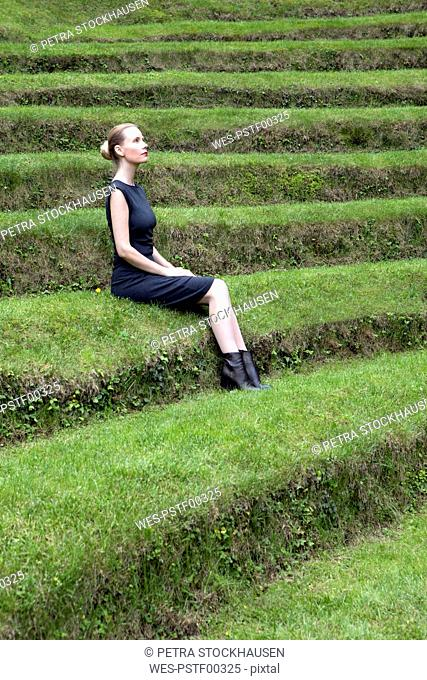 Italy, Alto Adige, Lana, woman sitting on grass-covered steps of natural open air theater