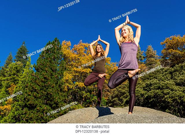 Fitness models doing yoga on a boulder, Pinecrest Lake; California, United States of America