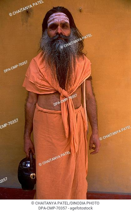 Sadhu priest wearing saffron clothes near the river ganges in the oldest city of India , Banaras now Varanasi , Uttar Pradesh , India