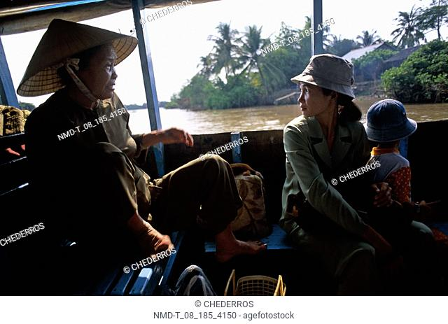 Mid adult woman and a young woman with her daughter sitting in a boat, Vietnam