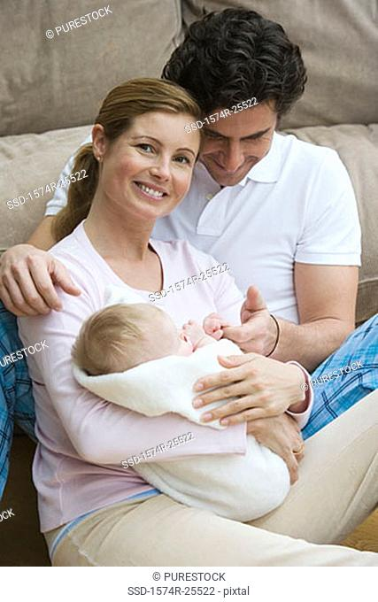 Mid adult woman holding her baby with a mid adult man sitting beside her