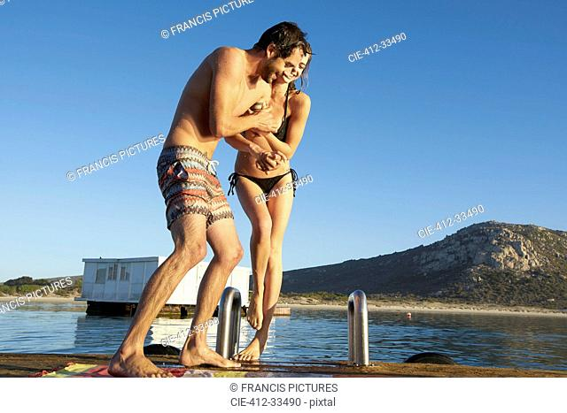 Young couple in bikini and swim trunks playing on sunny summer ocean dock