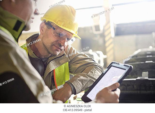 Steelworkers using digital tablet in steel mill