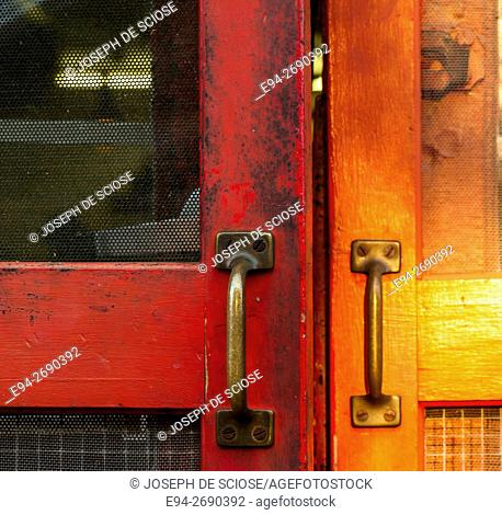 Close of 2 metal handles on an old wooden screen door. Atlanta, Georgia, USA