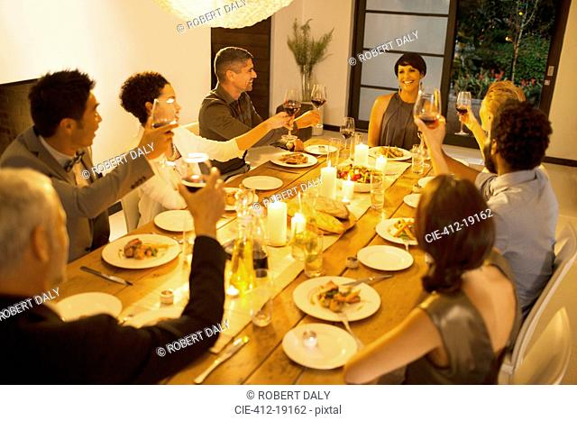 Friends toasting each other at dinner party