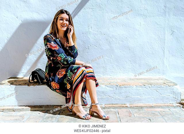 Spain, Cadiz, Vejer de la Frontera, portrait of fashionable woman on the phone sitting on wall