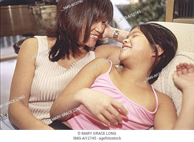 Mother and daughter sitting and smiling at each other