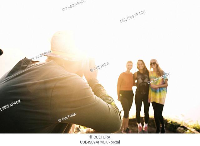 Young man photographing female friends at Lake Atitlan on digital camera, Guatemala