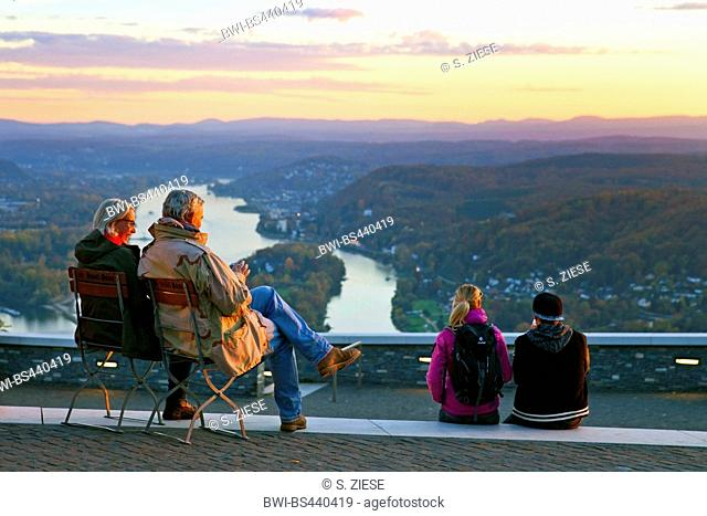 two couples sitting at Drachenfels and enjoying the view to Rhine at sunset, Germany, North Rhine-Westphalia, Siebengebirge, Koenigswinter