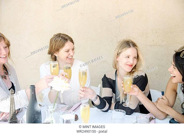 Four smiling women sitting at a table, holding glasses of champagne, toasting