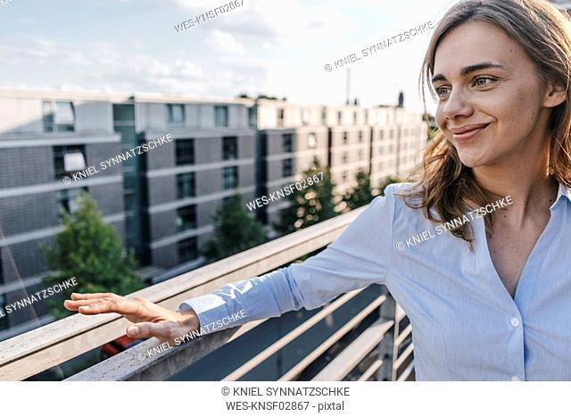 Businesswoman standing on terrace of industrial building