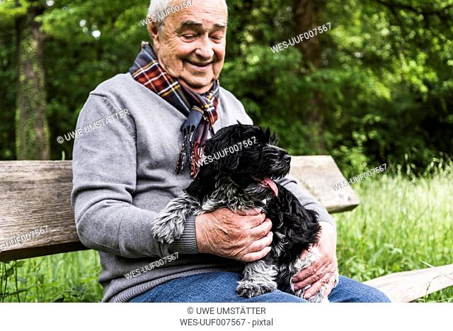 Smiling senior man sitting with his dog on a bench in nature