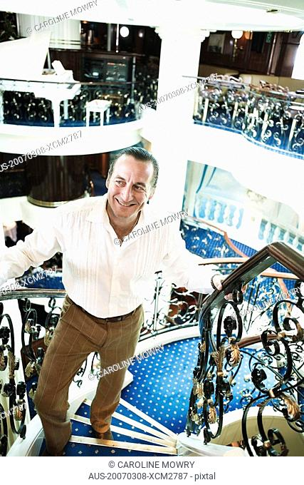 Mid adult man moving up on a staircase and smiling in a ship
