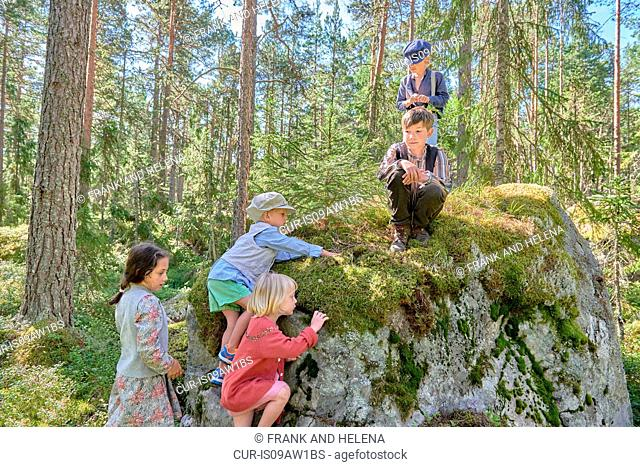 Boys and girls wearing retro clothes climbing forest boulder