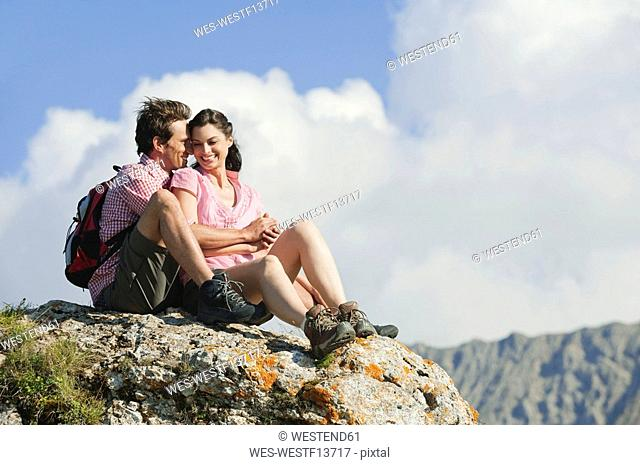 Italy, South Tyrol, Hiker couple sitting on rock
