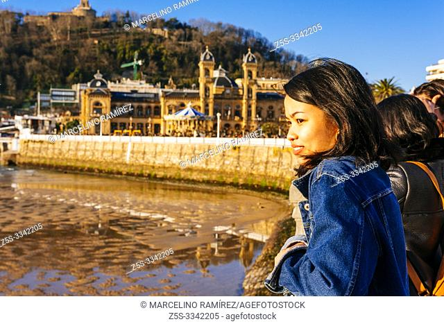 Young asian woman enjoying the last rays of the sun on the promenade of La Concha, in the background, the Nautical Club, the marina and Mount Urgull