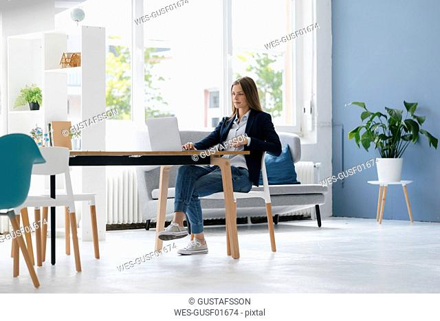 Young businesswoman sitting in office, using laptop