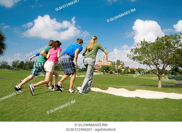 Five friends having fun in a golf course, Biltmore Golf Course, Coral Gables, Florida, USA