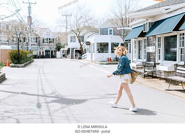 Young woman crossing road, portrait, Menemsha, Martha's Vineyard, Massachusetts, USA