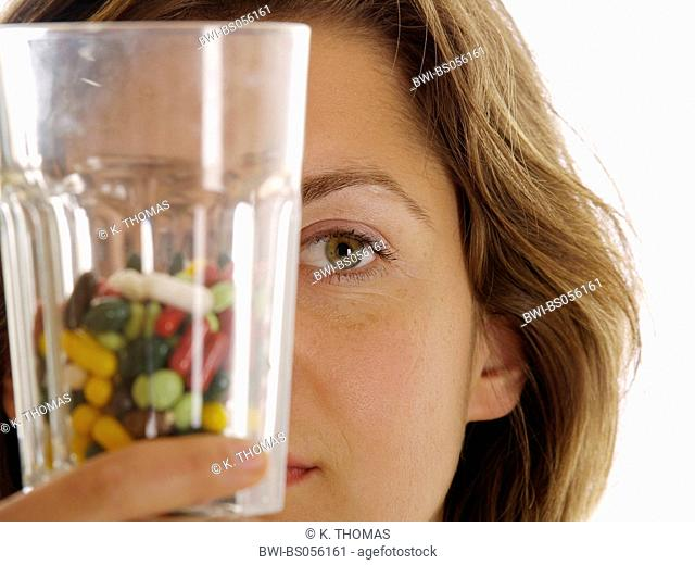 young woman / twen, holding a glass full of colourful pills high, half of the face visible