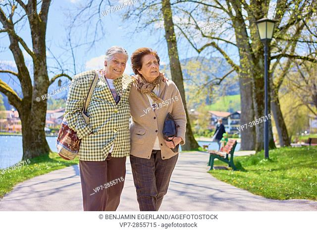 Optimistic senior woman walking with old friend in strong company in park, Bavaria, Germany