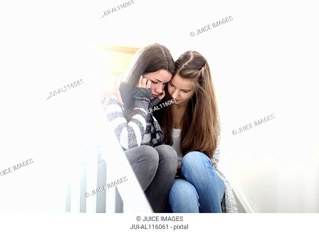 Teenage girl consoling friend