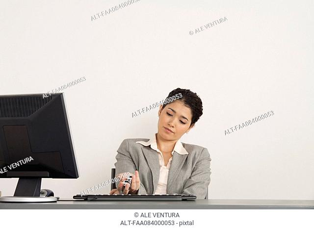 Young businesswoman holding yin yang balls at desk