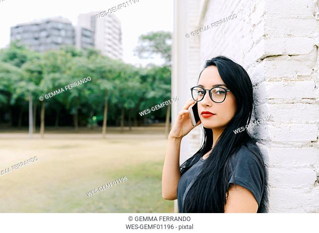 Portrait of young woman on cell phone in front of brick wall