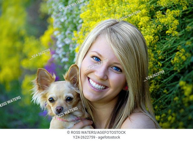 A young woman outdoors with her chihuahua