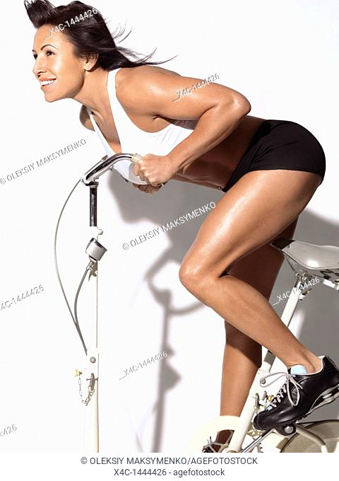 Fitness woman in her forties on an exercise bike