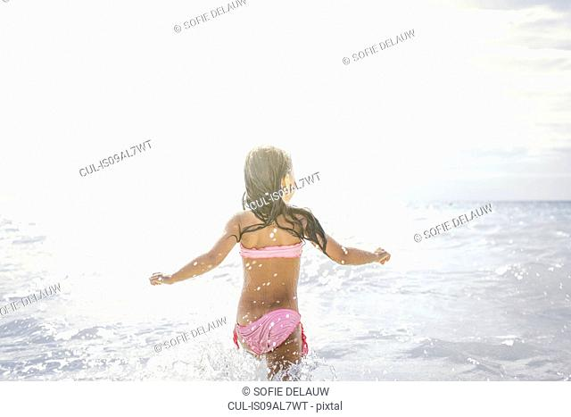 Rear view of girl running and splashing in sea, Tuscany, Italy