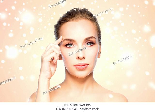 beauty, people, winter and plastic surgery concept - beautiful young woman showing her forehead over beige background and snow