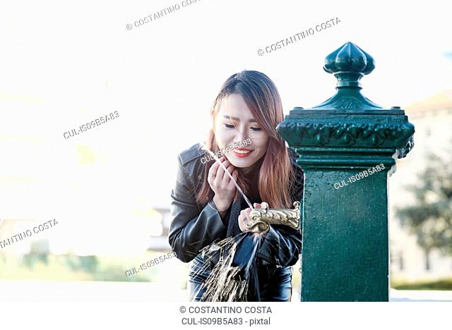 Young woman at drinking fountain, Milan, Italy