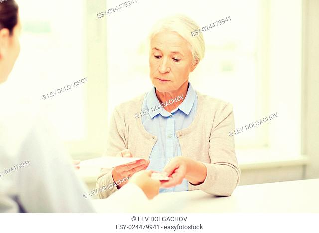 medicine, age, health care and people concept - doctor giving prescription and pills to senior woman at hospital