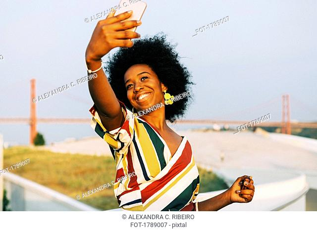 Confident young woman taking selfie with smart phone with 25 de Abril Bridge in background