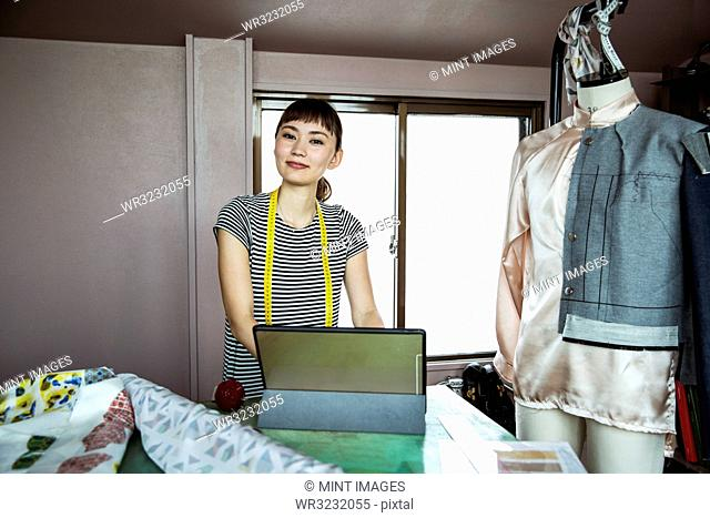 Japanese female fashion designer working in her studio, smiling at camera