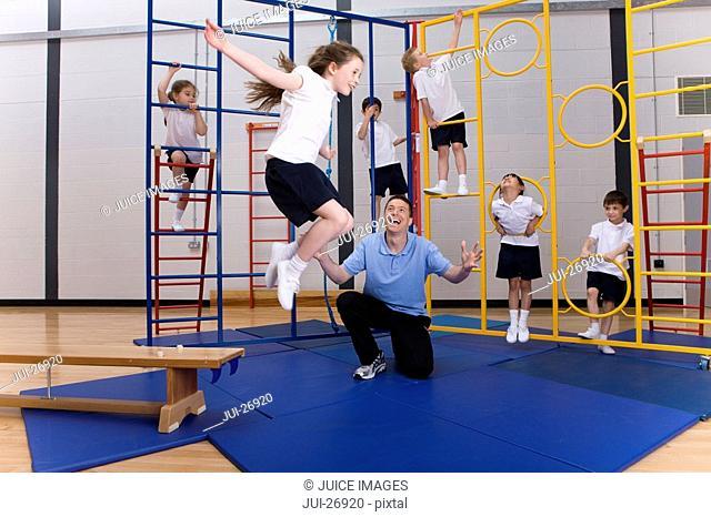 Gym teacher watching school girl jumping off climbing equipment