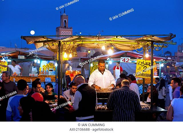 Morocco, Cook serving food at stall in Djemaa el-Fna Square; Marrakech