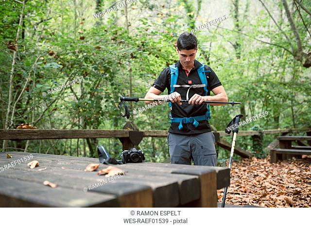 Man preparing walking sticks to start hiking in forest