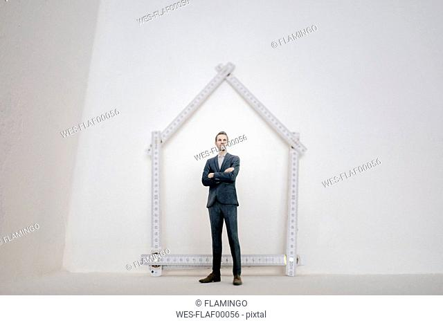 Businessman figurine standing on table with pocket rule, shaping a house