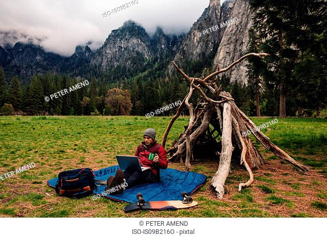 Hiker sitting by den using laptop, Yosemite, California, USA