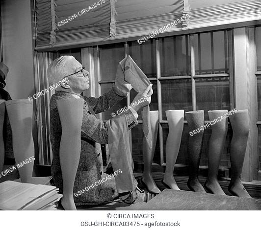 David H. Young, Agriculture Department Fabric Technician, Examining Cotton Stockings, which is trying to be Popularized over Silk and Nylon, Washington DC, USA