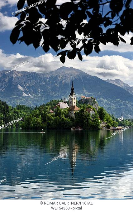 Paddleboarder on Lake Bled with Assumption of Mary church on Bled Island and St Martin church and Veliki Stol peak Karawanks mountain Slovenia