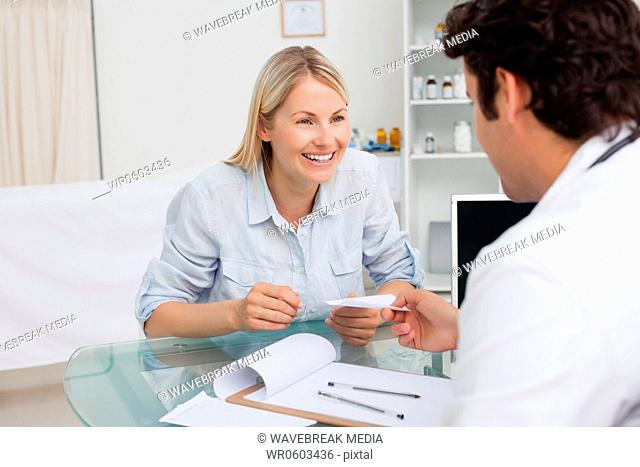 Happy woman getting prescription from her doctor