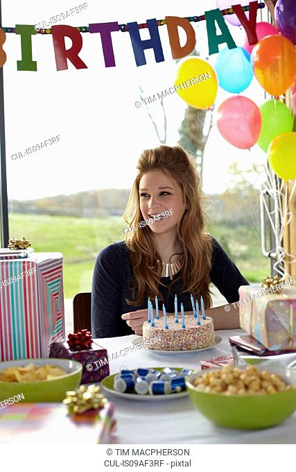 Teenage girl at table with birthday cake