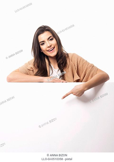 Happy woman pointing at empty whiteboard. Debica, Poland