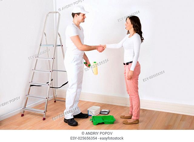 Young Beautiful Woman Shaking Hands To Painter With Paint Roller At Home