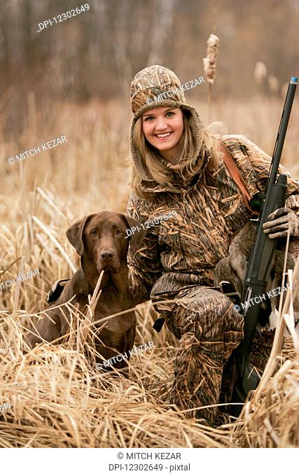 Female Waterfowl Hunter With Rifle And Rusty Yellow Lab