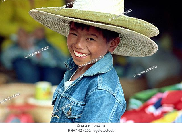 Portrait of a smiling boy wearing a denim jacket and two straw hats in Baguio City, northern Luzon, the Philippines, Southeast Asia, Asia